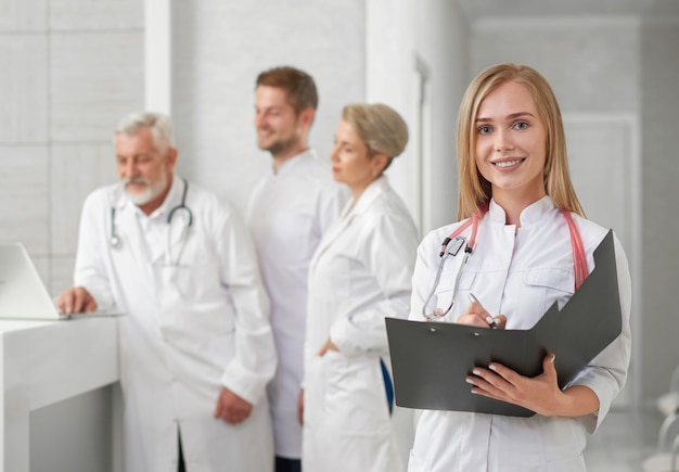 Doctor posing, smiling, while medical staff standing behind. Premium Photo
