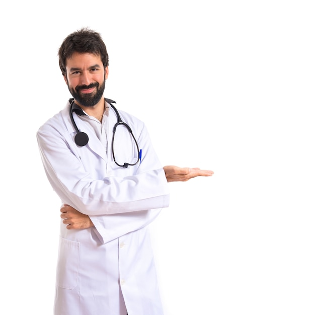 Doctor presenting something over isolated white background Free Photo