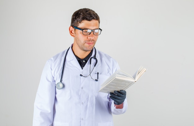 Doctor reading book in medical white robe Free Photo