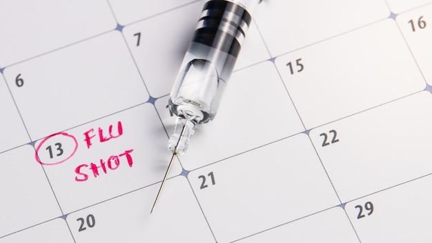 Doctor reminder flu shot in calendar with syringe, medicine and vaccine concept Premium Photo