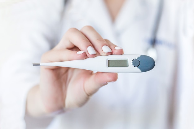 Doctor's hand holding electronic thermometer, close-up Premium Photo