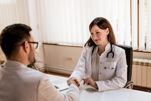 Doctor shaking hands to the male patient in the office Premium Photo