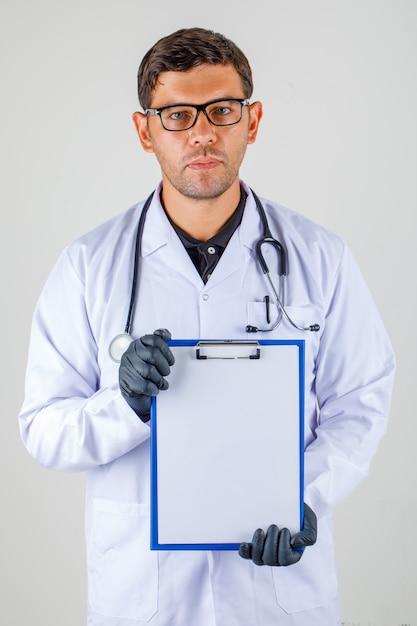 医師の医療白衣で空のクリップボードを表示 無料写真