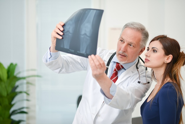Doctor showing a radiography to his patient Premium Photo