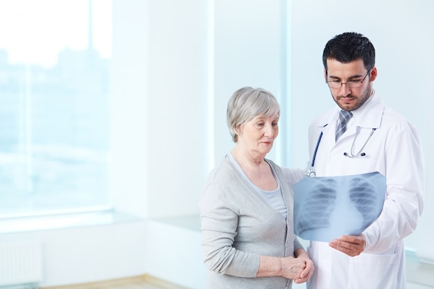 Doctor showing an x-ray to elderly patient Free Photo