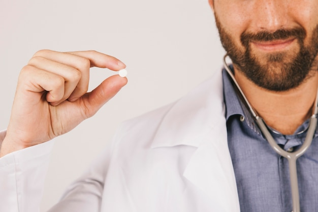 Doctor smiling and holding a pill Free Photo