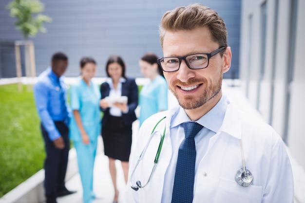 病院の敷地内に立っている医者 無料写真