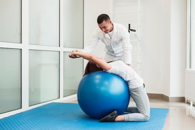 Doctor stretching patient on exercise ball Free Photo