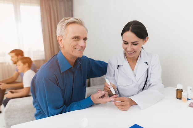 Doctor takes blood from elderly man's finger. Premium Photo