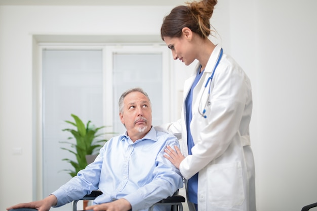 Doctor taking care of a patient on a wheelchair Premium Photo