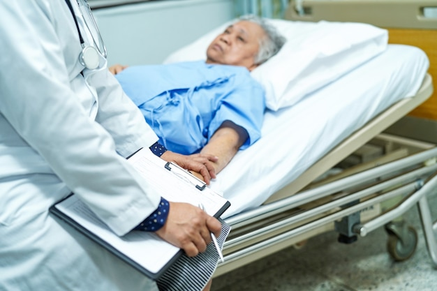 Doctor talking about diagnosis and note on clipboard with asian senior Premium Photo