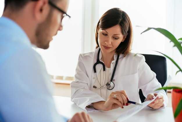 Doctor talking to her male patient at office, showing results Premium Photo