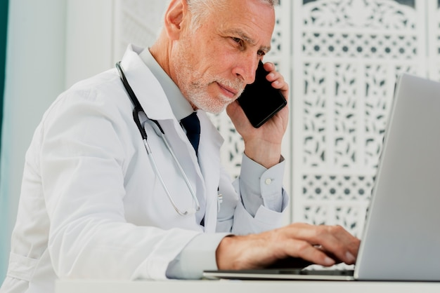 Doctor talking on his phone and using laptop Free Photo