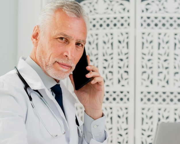 Doctor talking on the phone looking at camera Free Photo