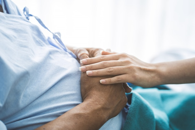 Doctor touching hands to encouragement mental of elderly patient after surgery at bed in hospital. Premium Photo