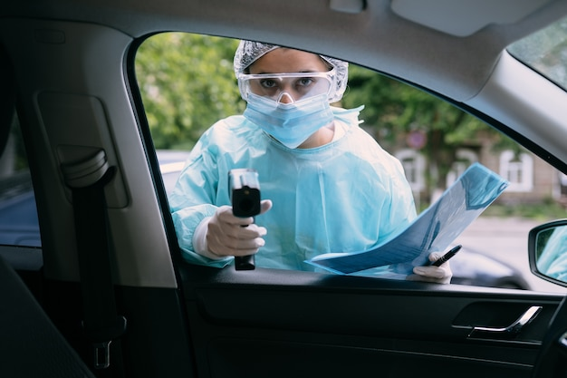 Il medico utilizza la pistola del termometro a infrarossi per controllare la temperatura corporea Foto Gratuite