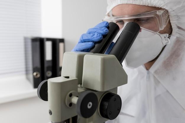 Врач с помощью микроскопа для проверки образца covid Бесплатные Фотографии