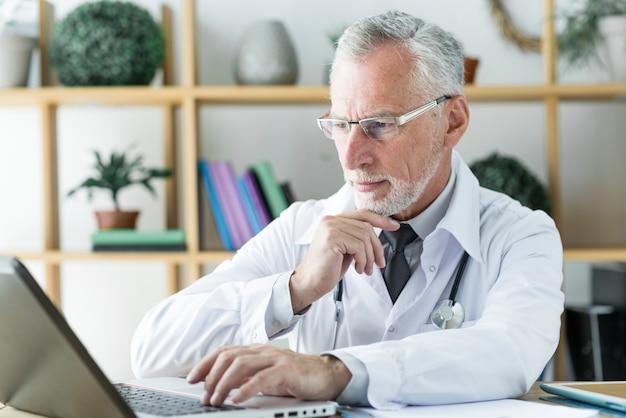 Доктор, используя ноутбук и мышление Бесплатные Фотографии