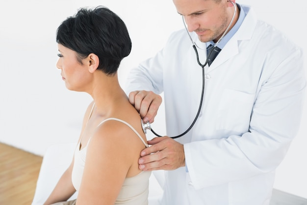 Doctor using stethoscope on back of patient Photo ...Doctor Stethoscope Comment