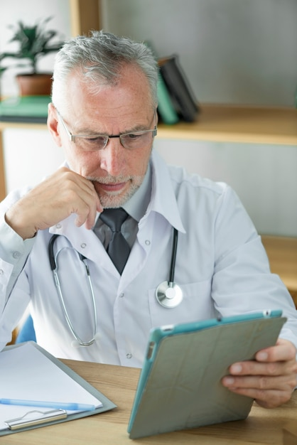 Doctor using tablet and thinking Free Photo