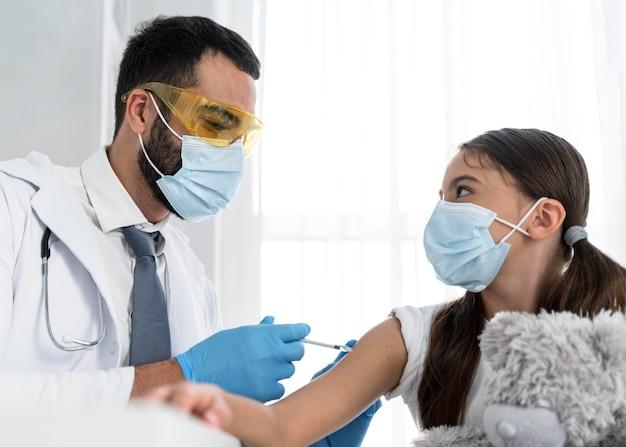 小さな女の子に予防接種をする医者 Premium写真