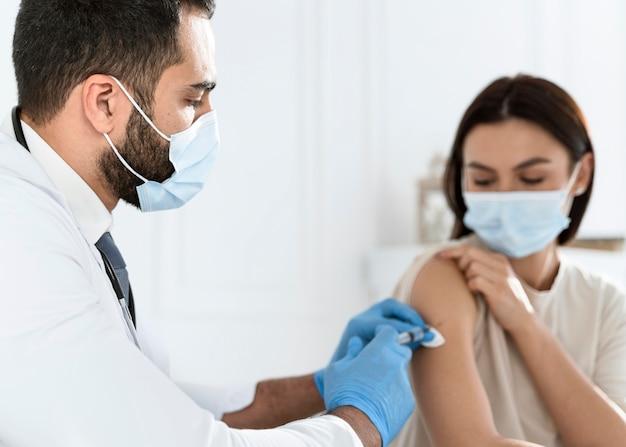 若い女性に予防接種をする医者 無料写真