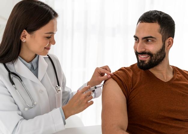 Medico che vaccina un bell'uomo Foto Gratuite