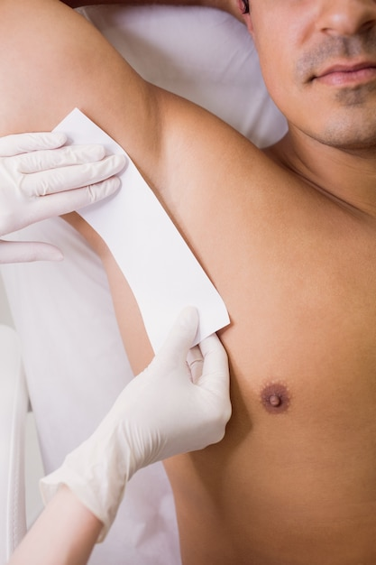 Doctor waxing male patient skin in clinic Free Photo