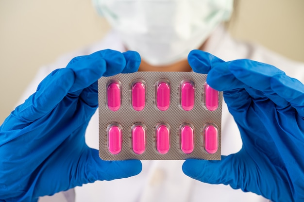 Doctor wear gloves and hold medicine panels. Free Photo