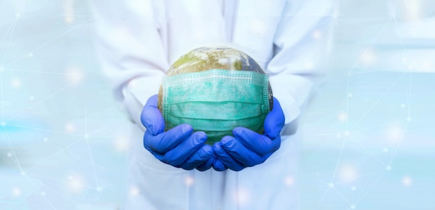 The doctor wear gloves holds the earth wearing mask to save from viruses banner Premium Photo