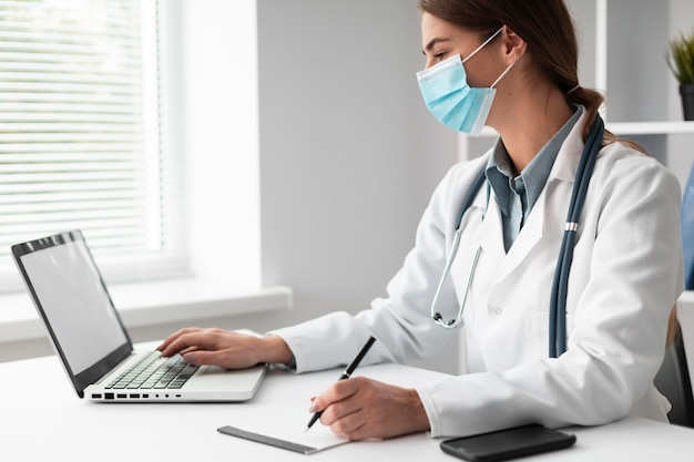 Doctor wearing face mask at the clinic Free Photo