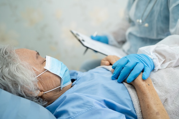 Ppe 정장을 입은 의사는 감염 Covid-19 코로나 바이러스를 보호하기 위해 병원에서 얼굴 마스크를 착용 한 아시아 노인 또는 노인 노부인 여성 환자를 확인합니다. 프리미엄 사진