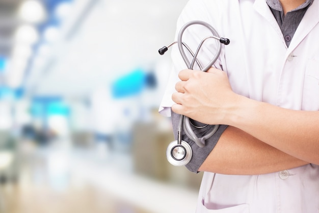Doctor with a stethoscope in the hands and hospital background Free Photo
