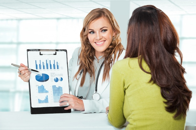 女性患者の医師。クリニックで患者に説明する聴診器でフレンドリーで幸せな医者 Premium写真