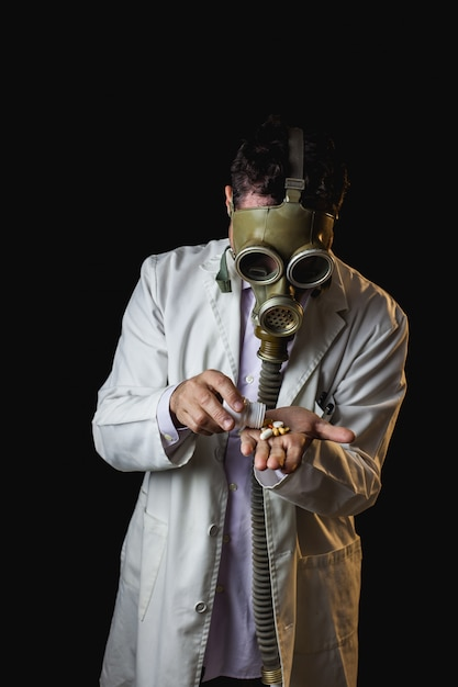 Doctor with gas mask taking pills from a bottle Premium Photo