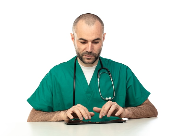 Doctor with green clothes uses a tablet sitting at a table. Premium Photo