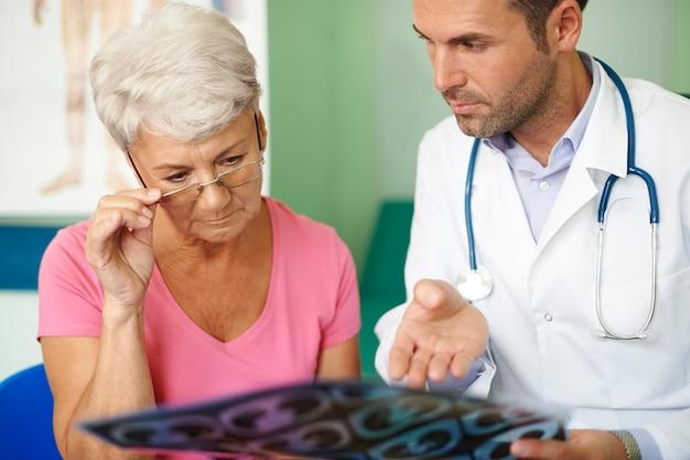 医療検査を分析する彼の先輩患者と一緒の医者 無料写真