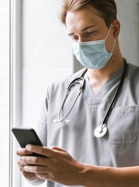 Доктор с медицинской маской проверяет смартфон Бесплатные Фотографии