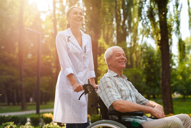 Doctor with old man in wheelchair laughing Premium Photo