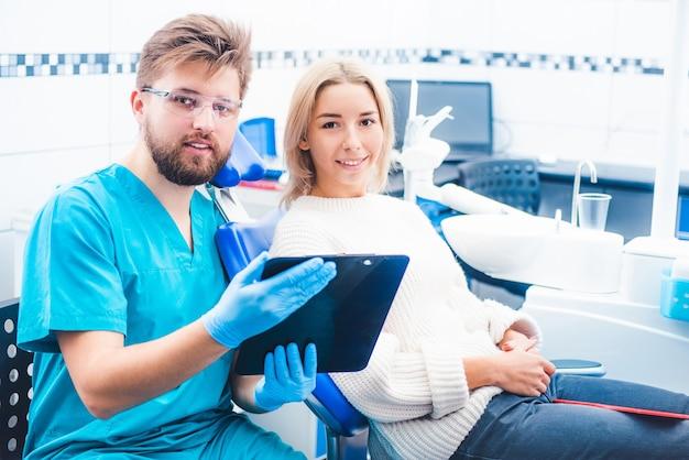 Врач с пациентом, читающий заметки из блокнота Premium Фотографии