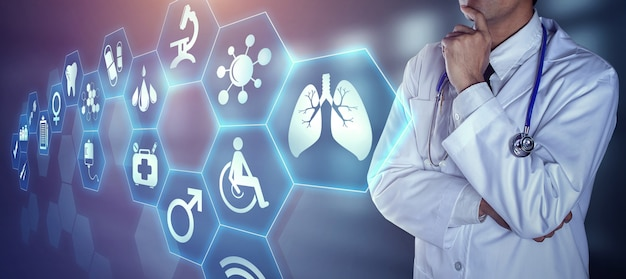 Doctor with stethoscope touching the digital icons Premium Photo