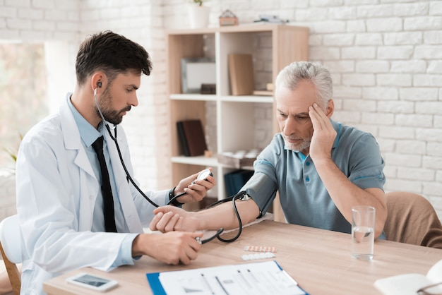 Doctor with tonometer measures blood pressure of elderly man Premium Photo