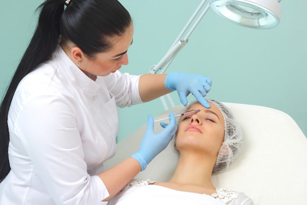 Doctor woman giving botox injections. Premium Photo