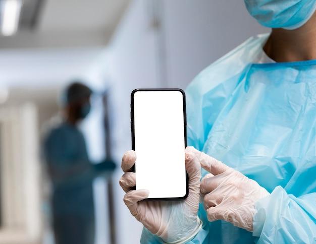 スマートフォンを指す防護服の医者の女性 Premium写真