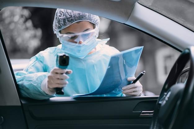 La donna del medico usa la pistola del termometro a infrarossi sulla fronte per controllare la temperatura corporea. Foto Gratuite