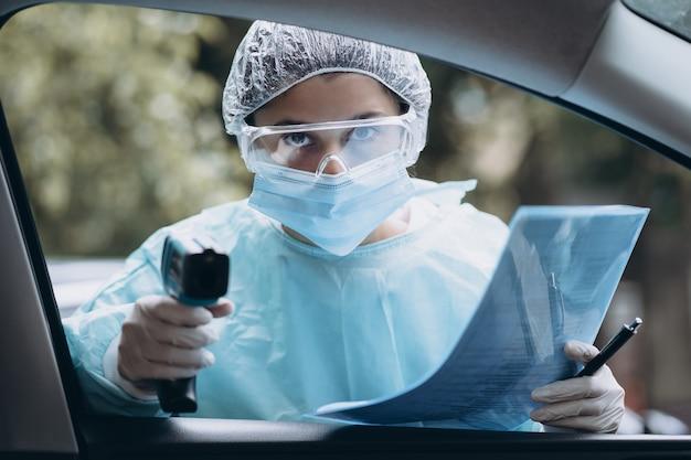 의사 여자는 적외선 이마 온도계 총을 사용하여 체온을 확인합니다. 무료 사진