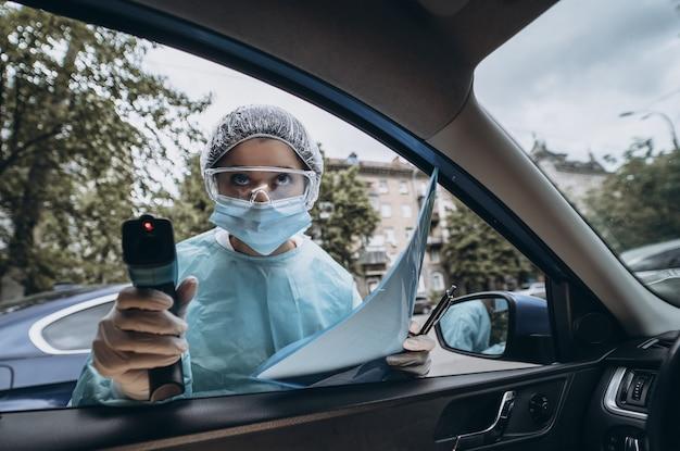 Medico donna usa la pistola termometro a infrarossi per controllare la temperatura corporea Foto Gratuite