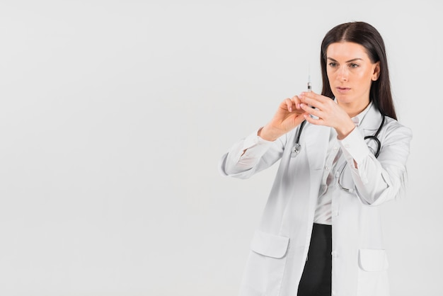 Doctor woman with serious face holding vaccination Free Photo