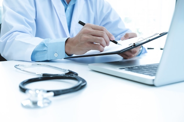 Doctor working with laptop computer and writing on paperwork. hospital background. Free Photo