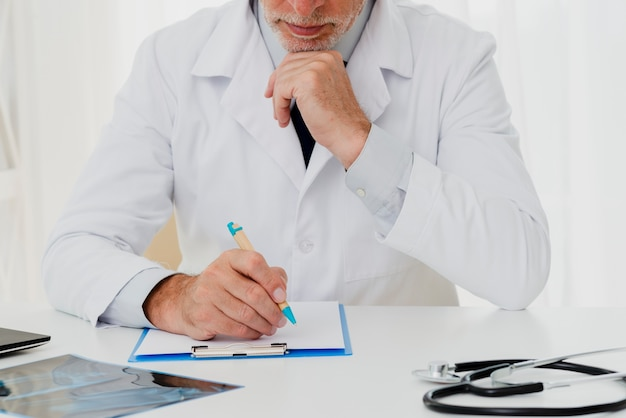 Doctor writing on clipboard with hand on chin Free Photo
